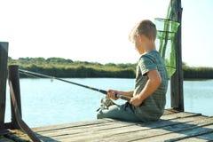Ragazzino che pesca da solo il giorno soleggiato immagine stock