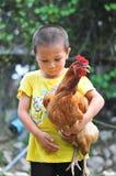 Ragazzino che porta un pollo nel suo armi Fotografia Stock