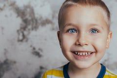 Ragazzino che posa davanti ad un muro di cemento grigio Ritratto di un bambino sorridente che porta una maglietta gialla immagine stock