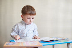 Ragazzino che si siede allo scrittorio e che legge un libro Immagine Stock