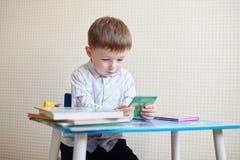 Ragazzino che si siede allo scrittorio e che legge un libro Fotografia Stock