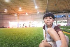 Ragazzino che si siede nel campo di formazione di calcio Fotografia Stock Libera da Diritti