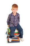 Ragazzino che si siede su un mucchio dei libri Fotografia Stock