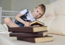 Ragazzino che si siede sul sofà con la pila di libro Fotografie Stock Libere da Diritti