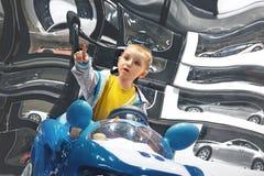 Ragazzino che si siede in un'automobile del giocattolo che mostra un dito fotografie stock libere da diritti