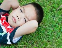 ragazzino che si trova su un'erba verde Immagini Stock Libere da Diritti