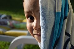 Ragazzino che sorride alla macchina fotografica dopo un bagno piacevole in una piscina Fotografia Stock