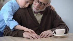 Ragazzino che sostiene nonno triste, abbracciante per confortarlo, cura della famiglia stock footage