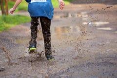 Ragazzino che spruzza in una pozza di fango, Fotografia Stock Libera da Diritti