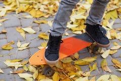 Ragazzino che sta su un pattino arancio all'aperto Ima del primo piano Fotografie Stock