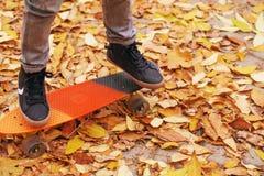 Ragazzino che sta su un pattino arancio all'aperto Ima del primo piano Fotografia Stock Libera da Diritti