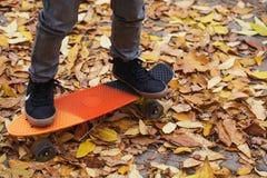 Ragazzino che sta su un pattino arancio all'aperto Ima del primo piano Fotografie Stock Libere da Diritti