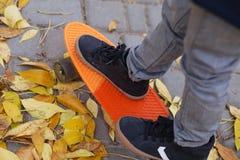 Ragazzino che sta su un pattino arancio all'aperto Ima del primo piano Fotografia Stock