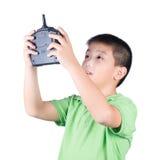 Ragazzino che tiene un telecomando radiofonico (microtelefono di controllo) per l'elicottero, il fuco o l'aereo isolati immagini stock