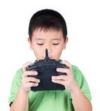 Ragazzino che tiene un telecomando radiofonico (microtelefono di controllo) per l'elicottero, il fuco o l'aereo isolati su fondo  immagine stock