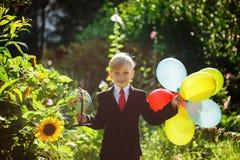 Ragazzino che va indietro al banco Ragazzo nel vestito Bambino con il globo ed i palloni variopinti sul primo giorno di scuola Fotografie Stock Libere da Diritti