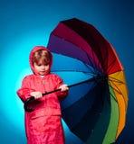 Ragazzino con dell'l'ombrello colorato d'arcobaleno isolato su fondo blu Bambino in pioggia E fotografia stock libera da diritti