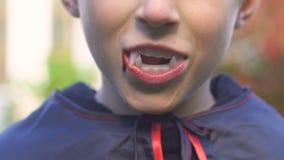 Ragazzino con i denti del vampiro che sorride alla macchina fotografica, festa in costume di Halloween, orrore archivi video