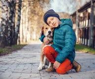 Ragazzino con il cane da lepre sulla via di autunno Fotografia Stock