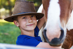 Ragazzino con il primo piano del cavallino fotografia stock libera da diritti