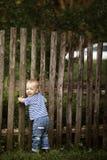 Ragazzino con il recinto all'aperto fotografia stock