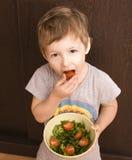Ragazzino con insalata ed il pomodoro Fotografia Stock