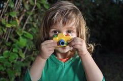 Ragazzino con la macchina fotografica del giocattolo Fotografia Stock