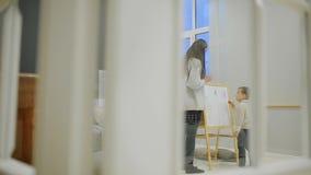 Ragazzino con la mamma in sua pittura per uso interno del salone sul bordo con gli indicatori un disegno del ` s del bambino Fami archivi video