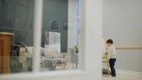 Ragazzino con la mamma in sua pittura per uso interno del salone sul bordo con gli indicatori un disegno del ` s del bambino Fami video d archivio