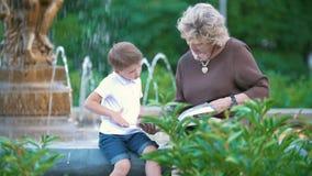 Ragazzino con la nonna che si siede alla fontana nel parco video d archivio