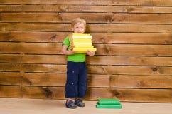 Ragazzino con la pila di libri alla parete di legno Fotografia Stock Libera da Diritti