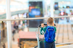 Ragazzino con lo zaino ed il carrello nell'aeroporto Immagini Stock