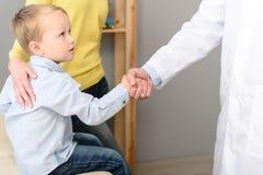 Ragazzino con sua madre al pediatra su consultazione immagine stock