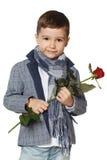 Ragazzino con una rosa in sue mani. Immagine Stock