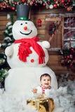 Ragazzino in costume del pupazzo di neve che si siede ad un interno della casa dal grande pupazzo di neve e dalla Santa aspettant Immagine Stock Libera da Diritti