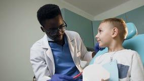 Ragazzino d'istruzione del giovane dentista africano come utilizzare spazzolino da denti facendo uso dei denti di plastica stock footage