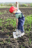 Ragazzino da scavare con la grande pala Fotografia Stock