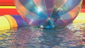 Ragazzino dentro una grande palla gonfiabile in acqua archivi video