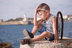 Ragazzino di pensiero in occhiali da sole e maglia che si siedono contro il porto marittimo Fotografie Stock