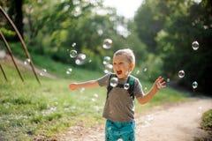 Ragazzino di risata felice con le bolle di sapone nel parco di estate sull'Unione Sovietica Fotografia Stock Libera da Diritti