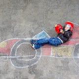 Ragazzino divertendosi con il disegno della macchina da corsa con i gessi Fotografie Stock Libere da Diritti