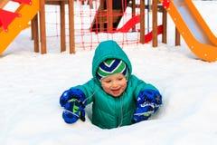 Ragazzino divertendosi nel campo da giuoco di inverno Fotografia Stock