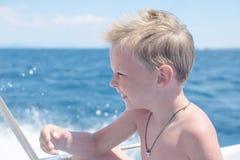 Ragazzino divertendosi sulla barca nel mare fotografia stock libera da diritti