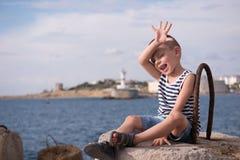 Ragazzino divertente che ondeggia la sua mano mentre sedendosi su un frangiflutti sui precedenti del mare Fotografie Stock Libere da Diritti