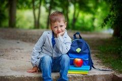 Ragazzino divertente che si siede sulla pietra con i libri, la mela e il backpac Fotografie Stock Libere da Diritti