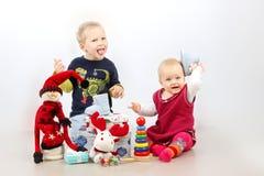 Ragazzino e bambina che giocano con i regali ed i giocattoli di Natale isolati sopra fondo bianco Fotografia Stock