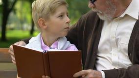 Ragazzino e libro di lettura di prima generazione, rilassantesi sul banco in parco, istruzione video d archivio