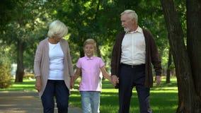 Ragazzino e nonni che camminano insieme nel parco, visita di fine settimana, tempo felice archivi video