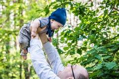 Ragazzino e padre che giocano all'aperto Fotografia Stock