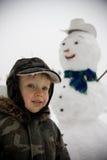 Ragazzino e pupazzo di neve Immagini Stock